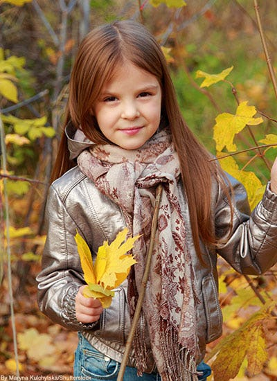 Little girl wearing metallic bomber jacket and neutral scarf in fall.