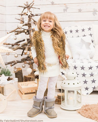Little girl wearing a holiday outfit and a faux fur vest.