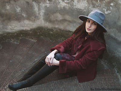 Stylish woman wearing a burgundy coat, gray felt hat, skinny jeans, and black tall riding boots.