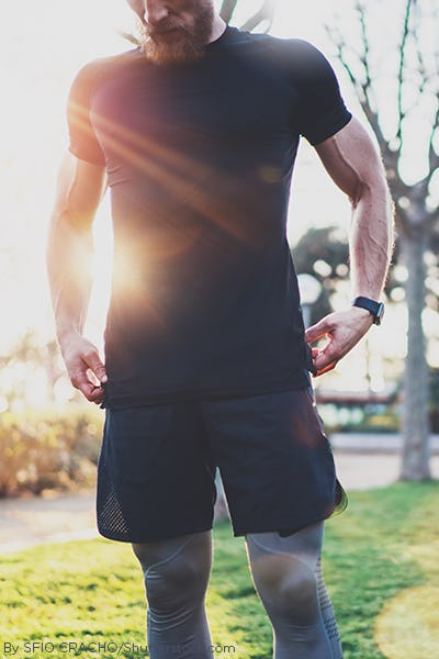 Man wearing a black shirt and black shorts with compression leggings