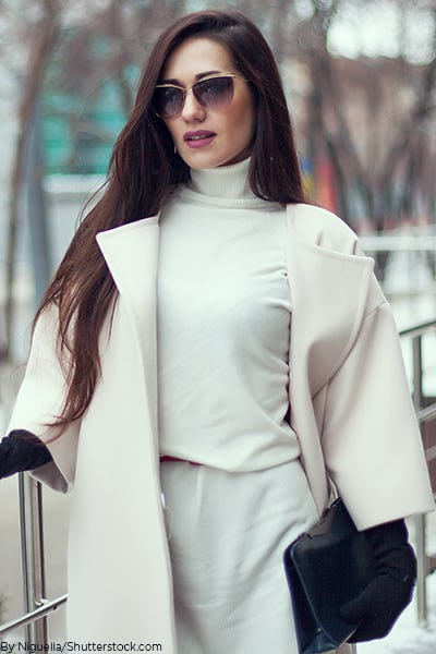 Young woman wearing a white trench coat