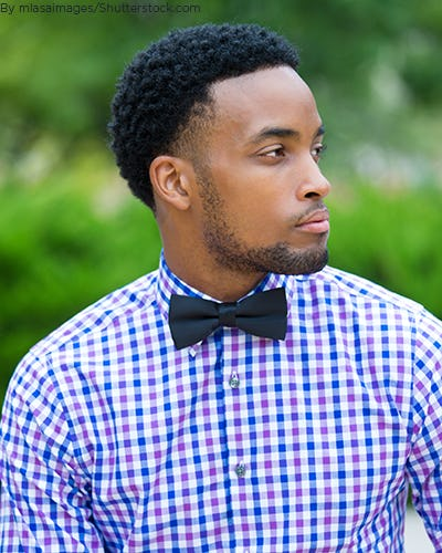 Young man wearing checkered shirt and matching bow tie