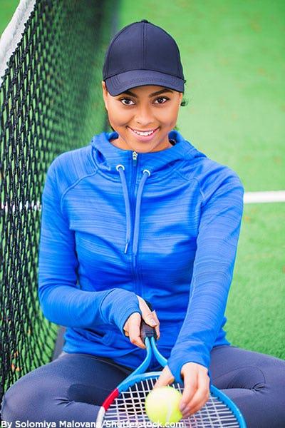 Woman wearing black baseball cap playing tennis.