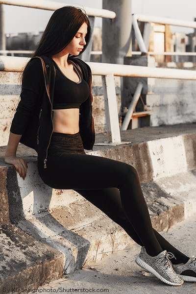 Woman wearing an all black workout outfit with black sports bra and black yoga pants