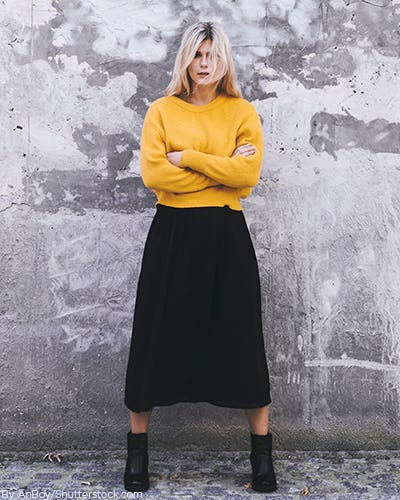 Young woman wearing a black pleated midi skirt with a mustard yellow sweater