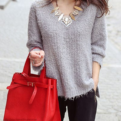 Woman wearing a gray fuzzy distressed sweater and chunky statement necklace whole holding a red leather handbag.