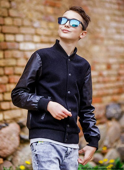Fashionable teen boy wearing sunglasses and a black leather and wool bomber jacket.