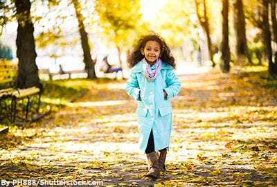 Little girl wearing a light blue coat, boots, and a scarf in fall.