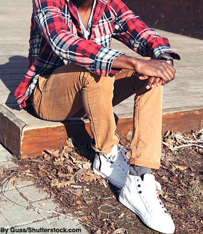 Stylish man wearing red flannel, chinos, and white high-top sneakers.