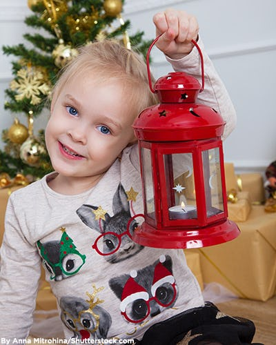 Little girl holding a holiday lantern and wearing a holiday themed screen tee.