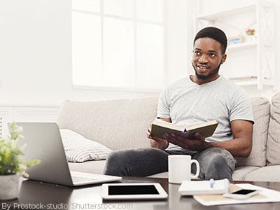 Young man sitting on the couch reading a book