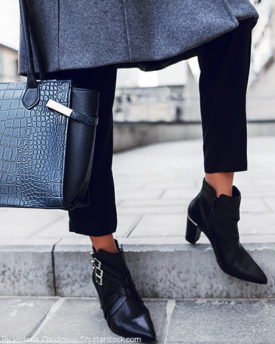 Woman wearing black ankle booties with matching black bag
