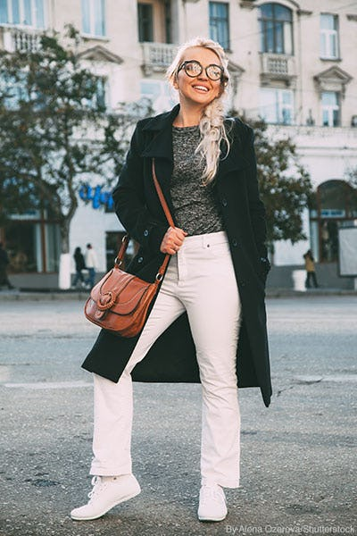 Stylish woman wearing white denim, black trench coat, and carrying a chestnut brown leather crossbody bag.