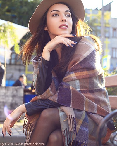 Young woman sitting on a park bench wearing a camel felt hat a navy dress with black tights and a plaid scarf being worn as a shawl