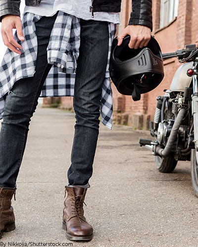 young man riding a motorcycle with a blue and white plaid shirt tied around his waist