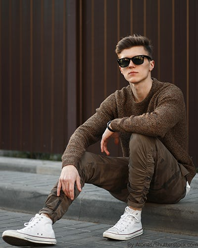 Young man wearing a an earthy brown crew neck sweater with matching brown jogger pants and white tennis shoes