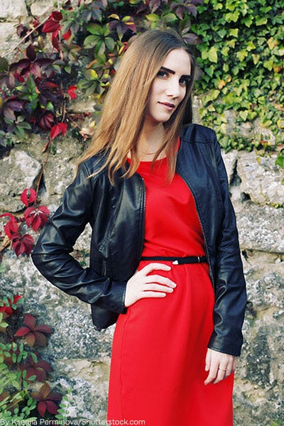 Woman in red belted dress and black leather jacket.