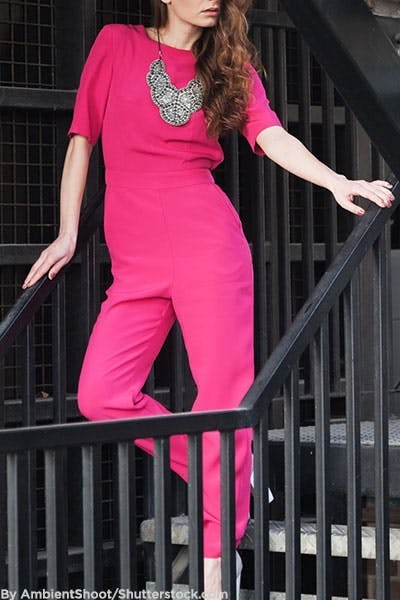 Woman in hot pink jumpsuit and statement necklace.