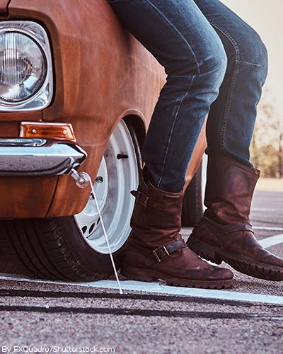 A young man leaning against a old school car wearing denim jeans and a pair of worn riding boots