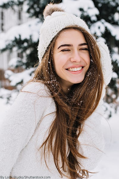 Young woman wearing a white sweater and white beanie playing in the snow