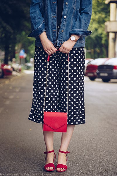Young woman wearing a black and white polka dot maxi skirt with a red purse and red strappy sandals