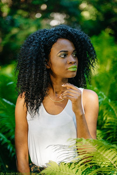Woman wearing a white tank top wearing green lipstick with greenery in the background