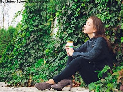 Woman sitting against an ivy wall wearing a gray sweater, black skinny jeans, and brown suede booties with a dipped front.