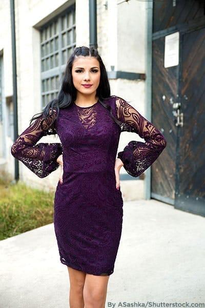 Woman wearing dark purple cocktail dress.