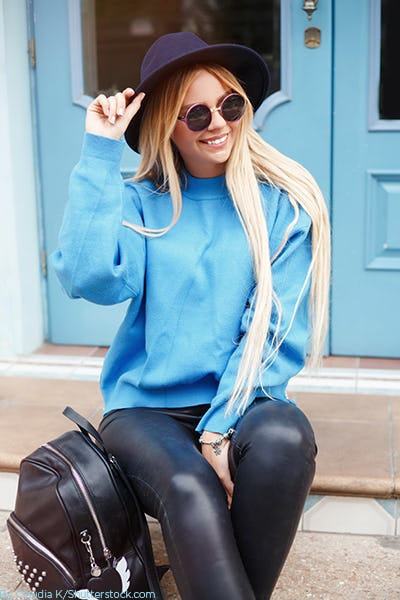 Young woman wearing a bright blue sweater paired with leather leggings