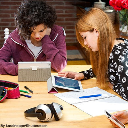 Group of college students studying at a library table with personal tablets and a pair of wireless headphones.