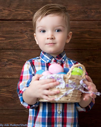 Little boy wearing a blue and red checkered shirt holding a basket of easter eggs