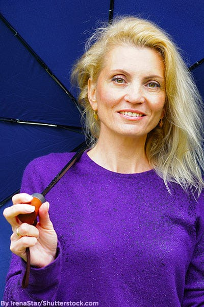 Mature woman wearing vivid purple sweater and holding umbrella.