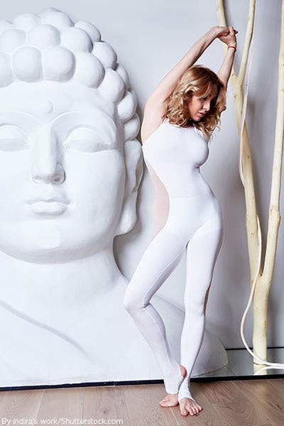 Woman doing yoga wearing a all white bodysuit