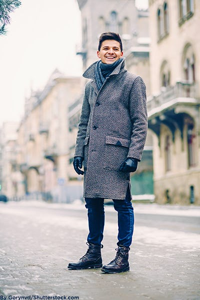 Fashionable man wearing a wool coat, scarf, leather gloves, and combat boots in the city.