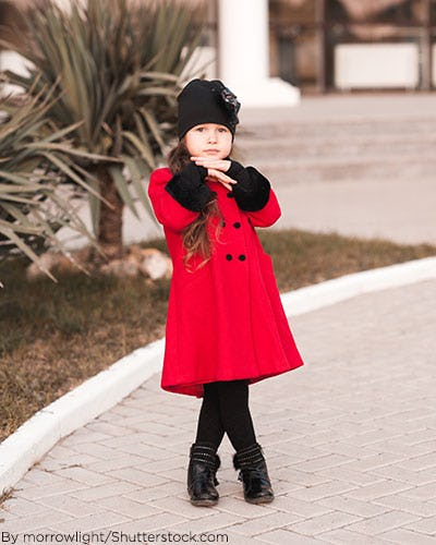 Little girl wearing red pea coat with black fur cuffs.