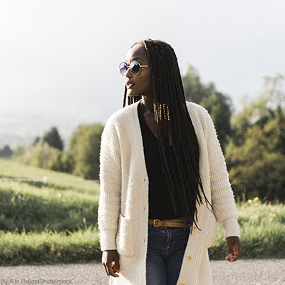 Woman wearing an oversized cream cardigan sweater outdoors.
