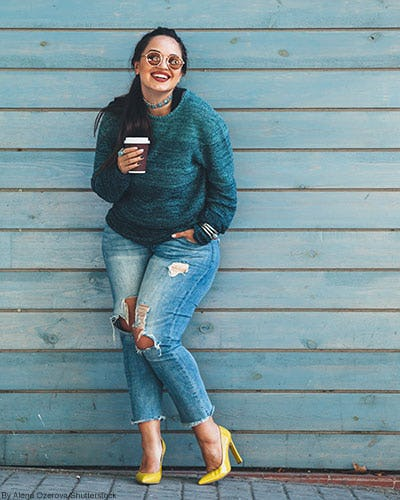 Woman holding a coffee cup and wearing a teal ombré fade sweater, distressed cropped jeans, and yellow heels.