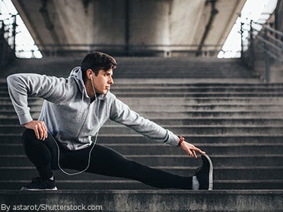 Young man working out and stretching in workout gear