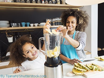 Mother and daughter in the kitchen making smoothies with juicer