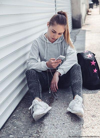Teen girl wearing fashionable athleisure at school.