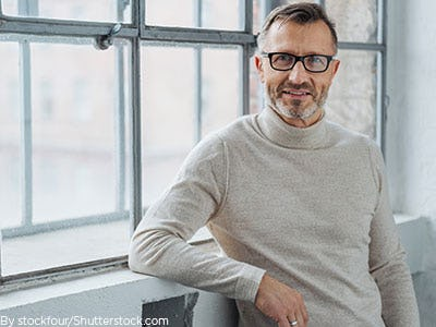 Older man leaning against the wall wearing a nice gray sweater