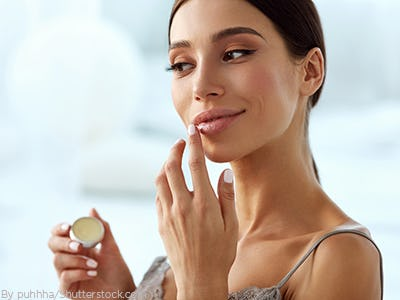 Woman looking in the mirror getting ready applying moisturizer and lip balm