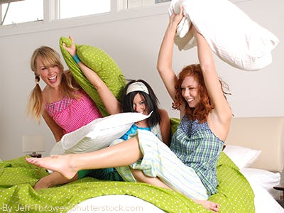 Three girls in a dorm room sitting on a bed with lime green bedding
