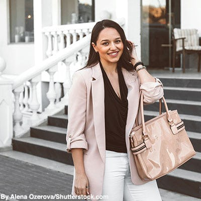 Stylish woman wearing a dusty pastel pink blazer and carrying a nude patent leather handbag.