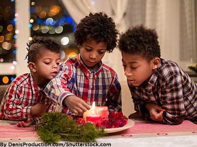 3 brothers wearing flannel shirts lighting holiday candles.