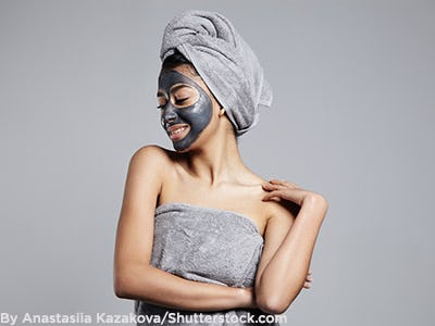 Woman wearing towel and face mask.
