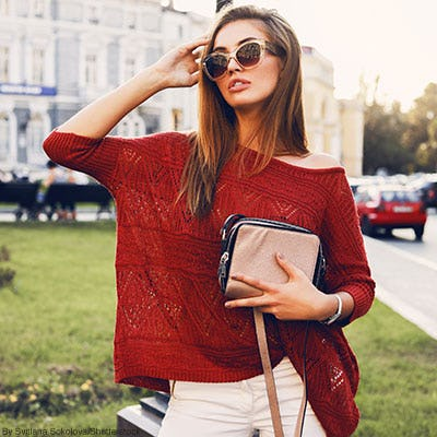Woman posing wearing a fashionable brick red textured knit sweater, fashion sunglasses, and a taupe crossbody purse.