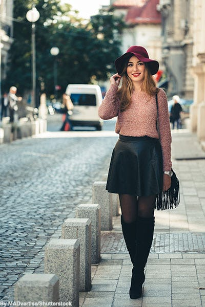 Fashionable woman wearing a pink pastel sweater, black skirt, black sheer tights, burgundy felt hat, fringe purse, and over-the-knee black suede boots.