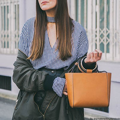 Trendy woman wearing a blue and white gingham choker neck blouse, black bomber jacket, and a ring-handle leather bag.