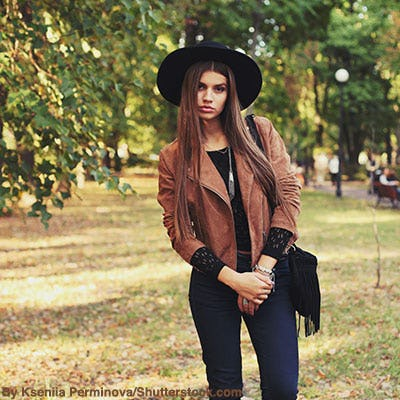 Stylish woman wearing a brown suede jacket, denim, black felt hat, and a black fringe purse.